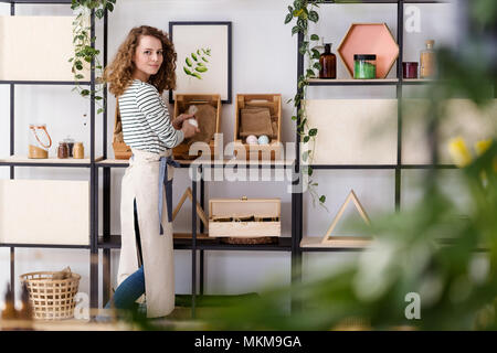 Smiling saleswoman arranging natural healthcare products on wooden boxes in the shop - Stock Photo