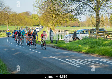 Male cyclists competing in Tour de Yorkshire 2018, racing on flat, scenic, countryside lane, followed by cars - Ilkley, North Yorkshire, England, UK. - Stock Photo
