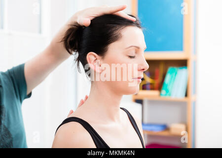 Woman having head massage from physiotherapist - Stock Photo