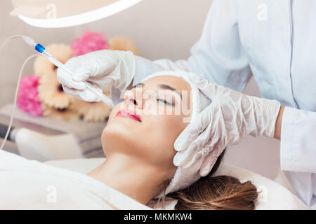Beautiful woman relaxing during non-invasive facial treatment - Stock Photo