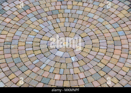 Bricks laid out in concentric circles in a yard. The layout creates an optical illusion of movement from the center/centre of the circle. Hypnotic. - Stock Photo