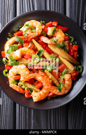 Fried prawns with pepper, garlic, corn cob and herbs close-up on a plate. Vertical top view from above - Stock Photo
