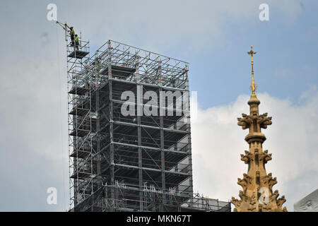 Workers at the top of scaffolding erected around the Elizabeth Tower, also known as Big Ben, during ongoing conservation works at the Houses of Parliament, Westminster, London. - Stock Photo