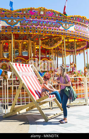 Women having fun in large deckchair by Vintage Fairground at Bournemouth, Dorset, UK in May - Stock Photo