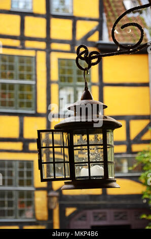 An old metallic lantern hanging from a yellow brick wall in Copenhagen, Denmark - Stock Photo