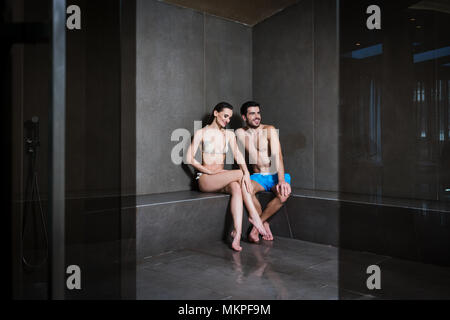 Young couple in love sitting in the steam bath of a modern spa center - Stock Photo
