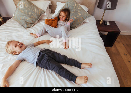 Little boy lying on bed with her sister sitting by holding a teddy bear smiling. Joyful little children playing in bedroom. - Stock Photo