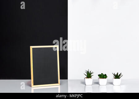 Wooden frame with black place for text. Mock up. Stylish room interior. Green plant in a white pot on black-white wall background - Stock Photo
