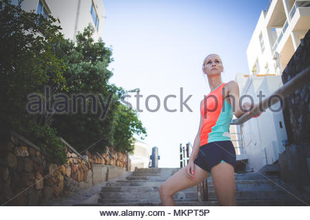 Blond female fitness model resting on some stairs during her exercise - Stock Photo