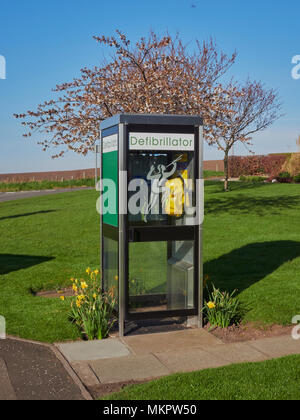 The Community Defibrillator in an Old telephone Box on the Village Green of East Haven in Angus, Scotland. A Community Initiative. - Stock Photo