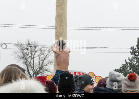TIRASPOL, MOLDOVA-FEBRUARY 18, 2018: Boy climbing on a wooden pole for the prize. Slavonic folk pagan holiday Maslenitsa (Shrovetide) - a symbolic mee - Stock Photo