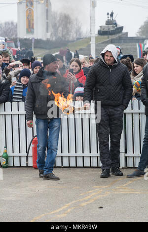 TIRASPOL, MOLDOVA - FEBRUARY 18, 2018: Men are preparing to set fire to the stuffed Shrovetide. The slavonic pagan holiday Maslenitsa (Shrovetide) - a - Stock Photo