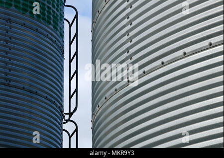 Industrial background of farm silos made from corrugated iron - Stock Photo