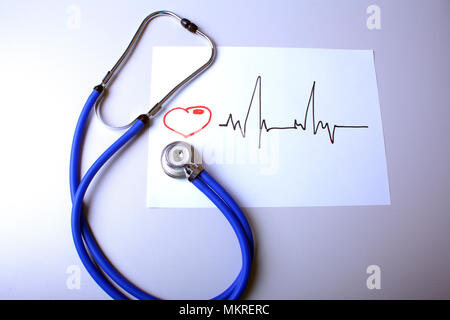 Cardiogram with medical stethoscope and doctor coat on table. - Stock Photo