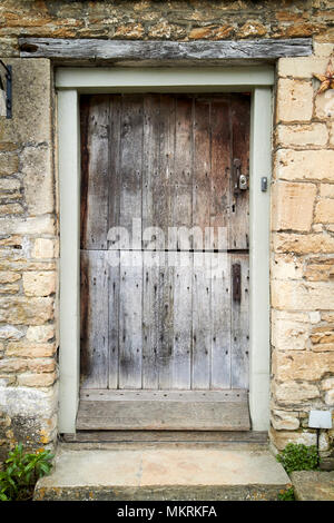 old worn weathered stable door on an old house Lacock village wiltshire england uk - Stock Photo