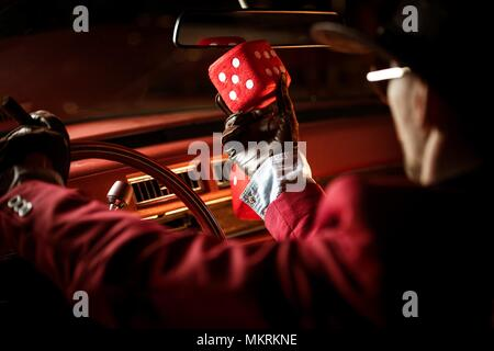 Casino Lucky Wish Concept. Casino Poker Player Talking to His Lucky Red Dice Inside the Classic Car. - Stock Photo
