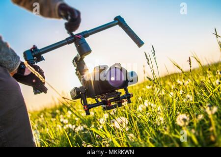 Video Camera Gimbal Stabilization Equipment. Digital SLR Videography Concept. Taking Shoots From the Gimbal. - Stock Photo