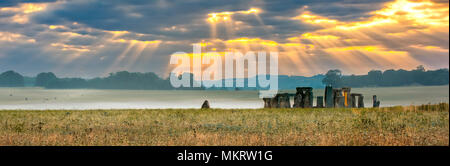 Amesbury, Wiltshire, United Kingdom - August 14, 2016: Cloudy sunrise over Stonehenge - prehistoric megalith monument arranged in circle. - Stock Photo