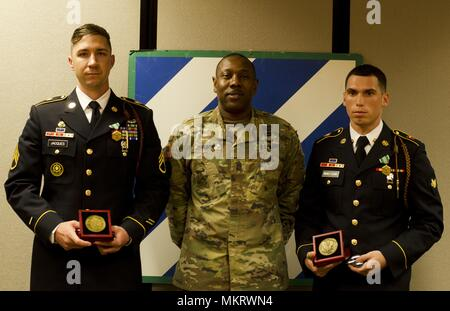 Command Sgt. Maj. John Johnson, the Task Force Marne, 3rd infantry Division command sergeant major, poses for a photo alongside this year's 3rd ID Noncommissioned Officer and Soldier of the Year winners at Fort Stewart, Ga. May 7, 2018, May 7, 2018. Staff Sgt. Joshua Jacques and Spc. Jamie Martinez-Feliciano, fire support specialists with 1st Battalion, 9th Field Artillery Regiment, 3rd Infantry Division Artillery will represent the Marne Division during the XIII Airborne Corps competition in June. (U.S. Army photo by Staff Sgt. Sierra A. Melendez, 50th Public Affairs Detachment, 3rd Infantry  - Stock Photo
