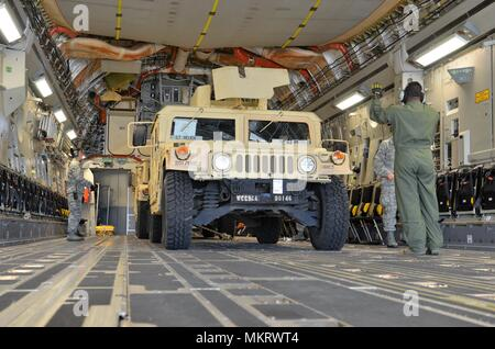 An Air Force loadmaster from the 62nd Airlift Wing at Joint Base Lewis-McChord, Wash. directs the loading of an M1151 Humvee (HMMWV) onto a C-17 Globemaster III May 7, 2018, May 7, 2018. The M1151 Enhanced Armament Carrier is an improved version of the standard HMMWV used to move troops. The movement is part of a field training exercise being conducted by the 201st Expeditionary Military Intelligence Brigade and is designed to provide more realistic load training for the Air Force and more airlift equipment preparation training for the Army. (U.S. Army photo by Staff Sgt. Chris McCullough). () - Stock Photo