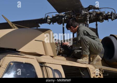 KANDAHAR AIRFIELD (May 8, 2018) -- An Afghan Air Force member inspects a UH-60 Blackhawk as air crews prepare for their first Afghan-led operational mission on this aircraft May 8, 2018, Kandahar Air Field, Afghanistan, May 8, 2018. The mission, which was in support of the elections, occurred just one day after the crews graduated from Mission Qualification Training. (U.S. Air Force photo/1st Lt. Erin Recanzone). () - Stock Photo