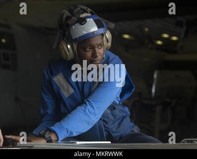 180507-N-AH771-0021 U.S. 5TH FLEET AREA OF OPERATIONS (May 7, 2018) Aviation Boatswain's Mate (Handling) Airman Khalyne Jones, from Marshall, Texas, drives an AS-32A spotting dolly in the hangar bay aboard the Wasp-class amphibious assault ship USS Iwo Jima (LHD 7), May 7, 2018, May 7, 2018. Iwo Jima, homeported in Mayport, Fla. is on deployment to the U.S. 5th Fleet area of operations in support of maritime security operations to reassure allies and partners, and preserve the freedom of navigation and the free flow of commerce in the region. (U.S. Navy photo by Mass Communication Specialist 3 - Stock Photo