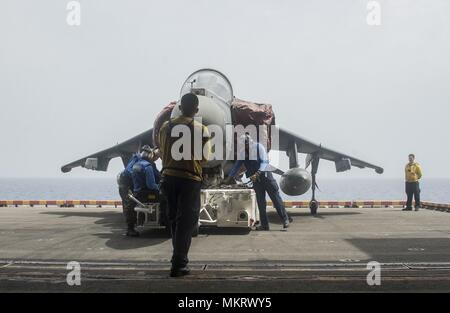 180507-N-AH771-0071 U.S. 5TH FLEET AREA OF OPERATIONS (May 7, 2018) Sailors aboard the Wasp-class amphibious assault ship USS Iwo Jima (LHD 7) prepare an AV-8B Harrier jet attached to Marine Medium Tiltrotor Squadron (VMM) 162 (Reinforced), to be moved into the ship's hangar bay, May 7, 2018, May 7, 2018. Iwo Jima, homeported in Mayport, Fla. is on deployment to the U.S. 5th Fleet area of operations in support of maritime security operations to reassure allies and partners, and preserve the freedom of navigation and the free flow of commerce in the region. (U.S. Navy photo by Mass Communicatio - Stock Photo
