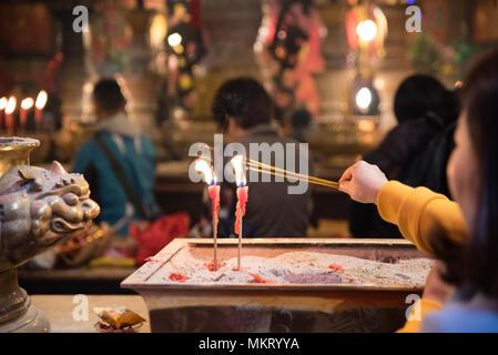 A woman lights a incense sticks from burning candles praying in famous Man Mo temple, Sheung Wan, Hong Kong