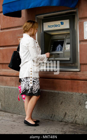A young blond woman taking out money from an ATM belonging to Bank Nordea in the city of Uppsala, Sweden. - Stock Photo