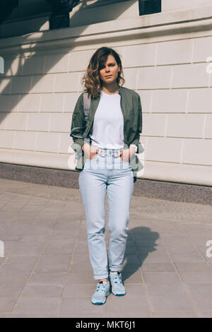 Young woman walking in the city with hands in pockets. Full height photo of fashionable female standing near the wall at sunny summer day. - Stock Photo