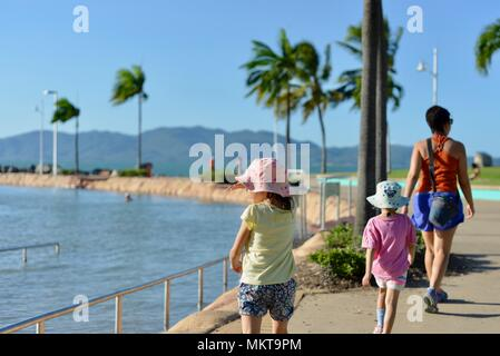 Mother and children walking together in the late afternoon around the rockpool, Jezzine barracks, Kissing point fort, Townsville Queensland, Australia - Stock Photo