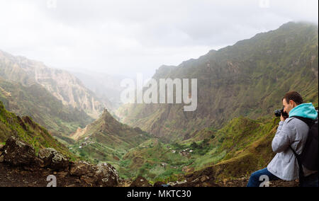 Traveler in front of motion landscape. Deep clouds above green Xo-Xo Valley. Santo Antao Island, Cape Verde - Stock Photo