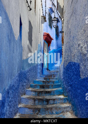 Stone staircase in a narrow aperture between the old blue walls of the medina of Chefchaouen, Morocco. - Stock Photo