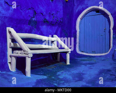 White wooden bench and door with a white outline contour against a blue wall background. - Stock Photo