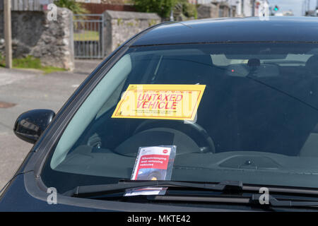 Clamped untaxed vehicle with notices on windscreen - Stock Photo