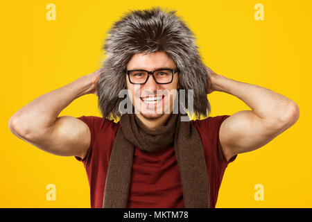 Cheerful handsome man wearing stylish furry hat and eyeglasses smiling at camera on yellow background.