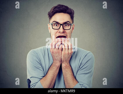 Young man in glasses having panic attack and looking with fear at camera on gray background. - Stock Photo