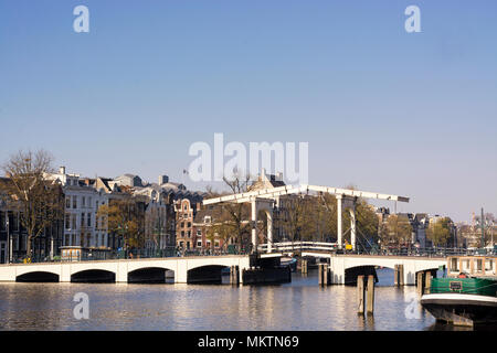 View on the Skinny Bridge over the river Amstel, in Amsterdam, capital of the Netherlands, on a sunny day - Stock Photo