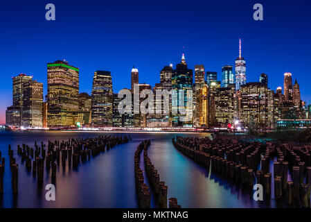 The NYC Skyline looking across from Brooklyn Bridge Park through the remains of the old piers - Stock Photo