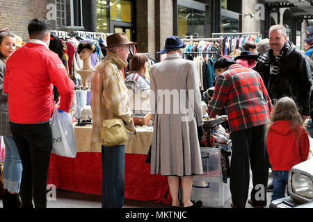 Rear view of couple in 1940s style clothing browsing market stall at the Vintage Car Boot Sale at Granary Square in Kings Cross London UK KATHY DEWITT - Stock Photo