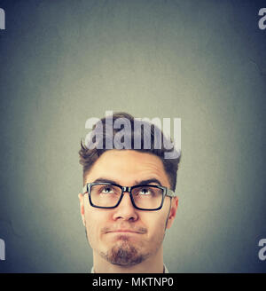 Serious young man wearing black glasses looking up thinking - Stock Photo