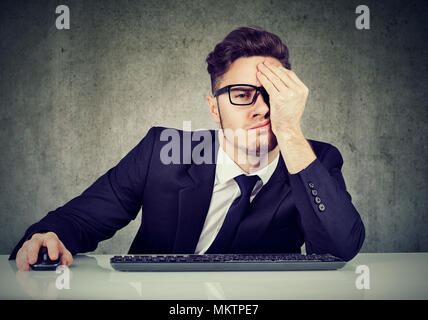 Young man in suit sitting at table in office looking desperate and exhausted. - Stock Photo