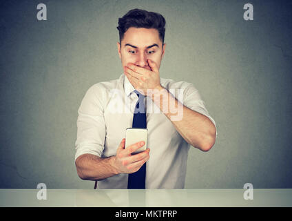 Casual young man covering mouth in shock while sitting and surfing smartphone realizing problem. - Stock Photo