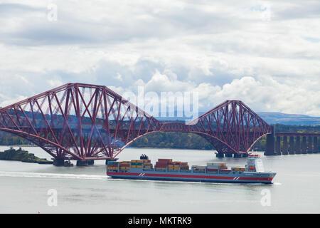 A cargo boat passing under the Forth rail Bridge near Edinburgh Scotland. - Stock Photo