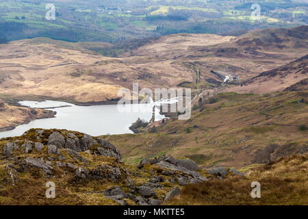 From just above Wysgan Quarry on the Moelwyn mountains in Snowdonia, steam can be seen rising from a narrow gauge train on the Ffestiniog railway as i - Stock Photo