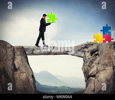 Businessman carries a piece of puzzle while he walking on a tree trunk. concept of missing piece - Stock Photo