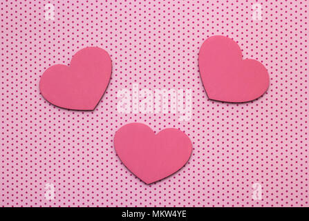 pink polka dots background and hearts from wood - Stock Photo