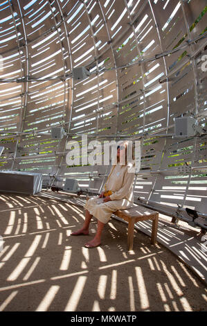 Woman listening to sounds of outer space in exhibit at the Huntington Gardens in Pasadena, CA - Stock Photo