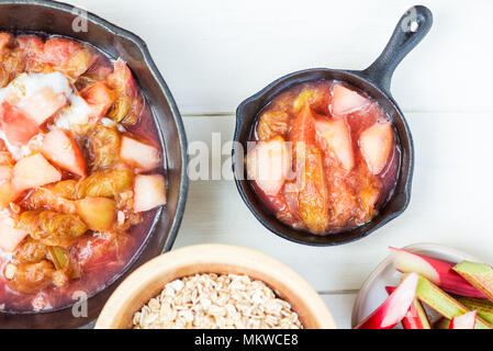 Homemade rhubarb and apple compote for making crumble in the cast iron pans - Stock Photo