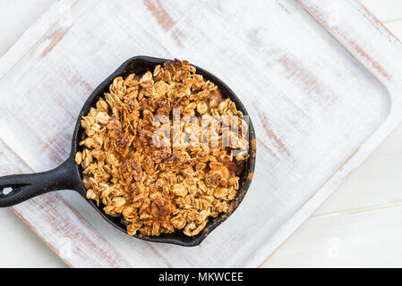 Homemade cooked rhubarb and apple crumble with oatmeal in the cast iron pans - Stock Photo